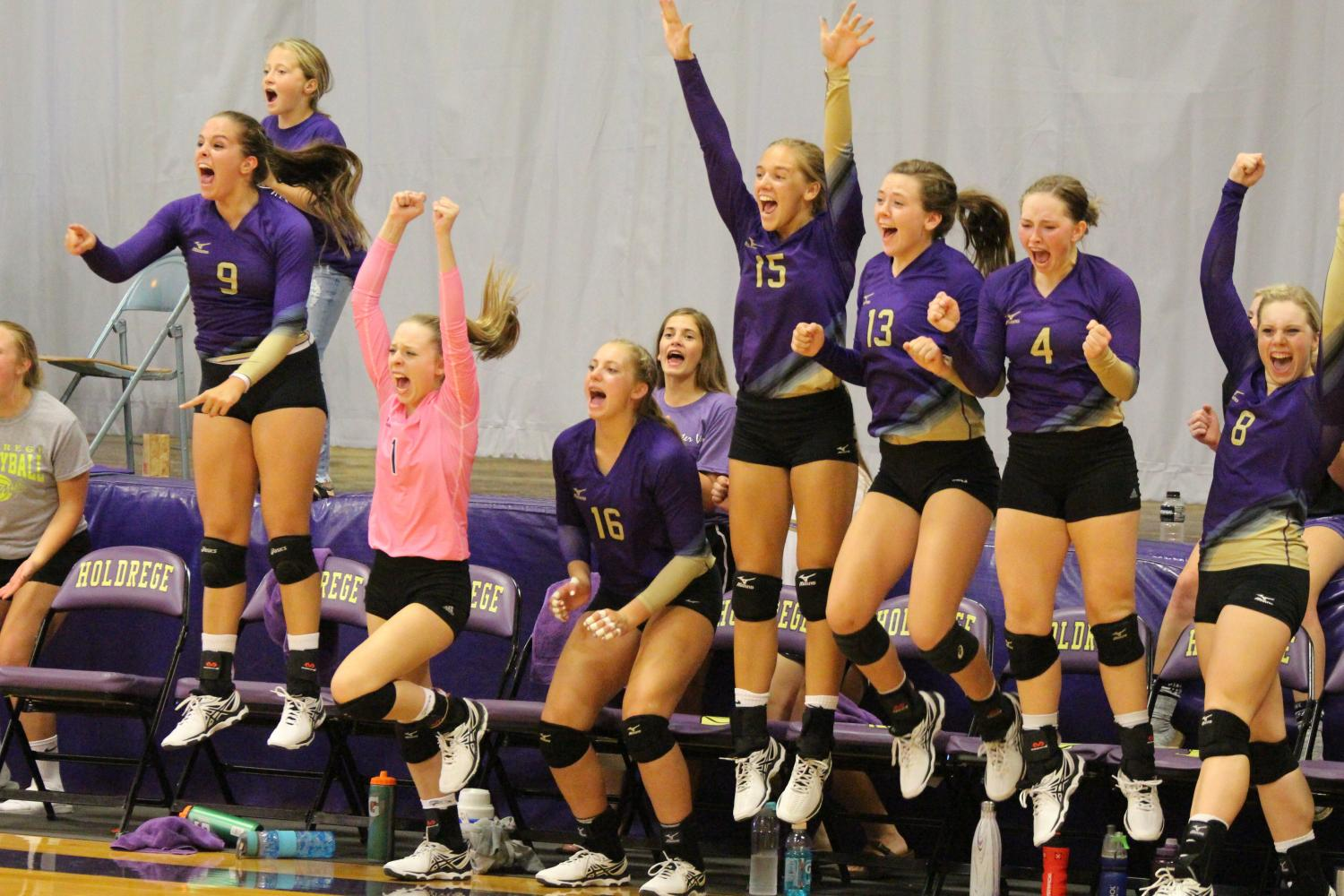 Reacting to big point, the Duster Volleyball bench cheers on their teammates.