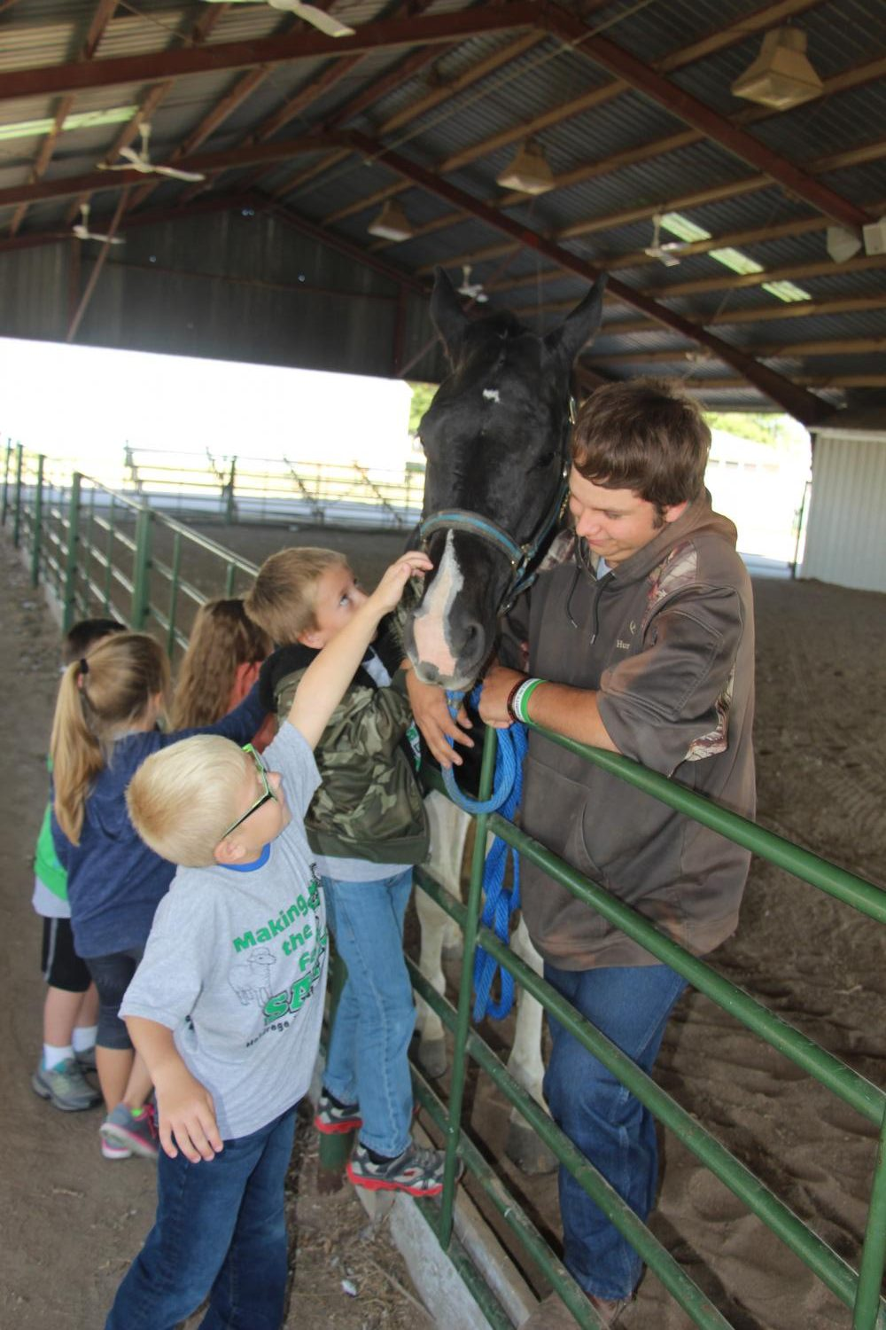 FFA member, Tyelar Samuelson holds onto a horse as an elementary student pets it.