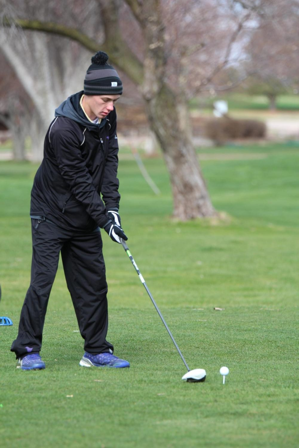 Senior Logan Neinast takes a practice swing before teeing off on Hole 5 during the Holdrege Invite.