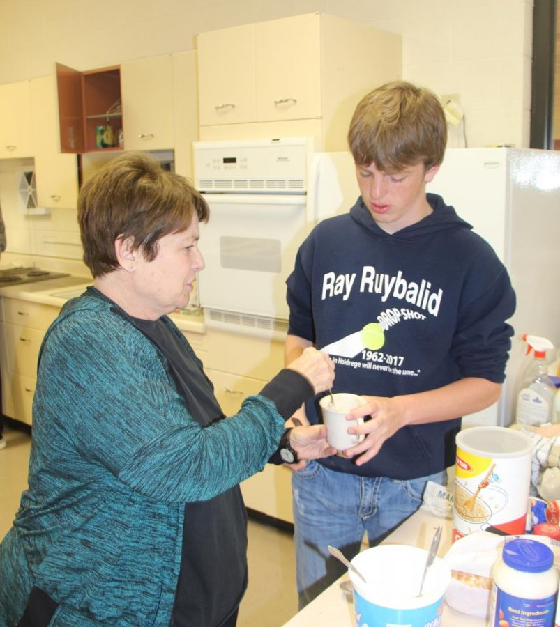 Family+Consumer+Science+teacher%2C+Mrs.+Erickson%2C+helps+sophomore+Harrions+Elliot+with+a+desert+dish+during+Foods+class.