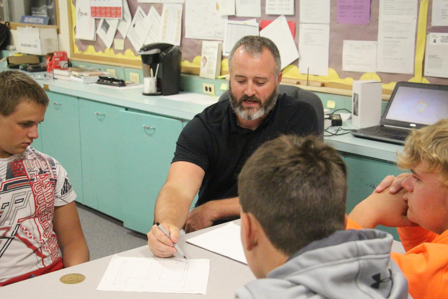 Helping students, Mr. Hoyt makes a point about an assignment.