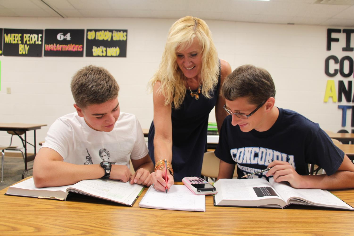 Looking over a Calculus problem, Mrs. Pearson helps Spencer Knuth and Caden Erickson.