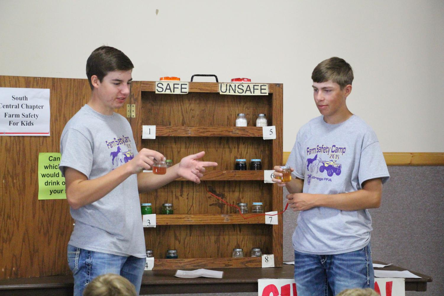 Brady Edgren and Eli Swanson present a safety station to first graders during the annual farm safety day.
