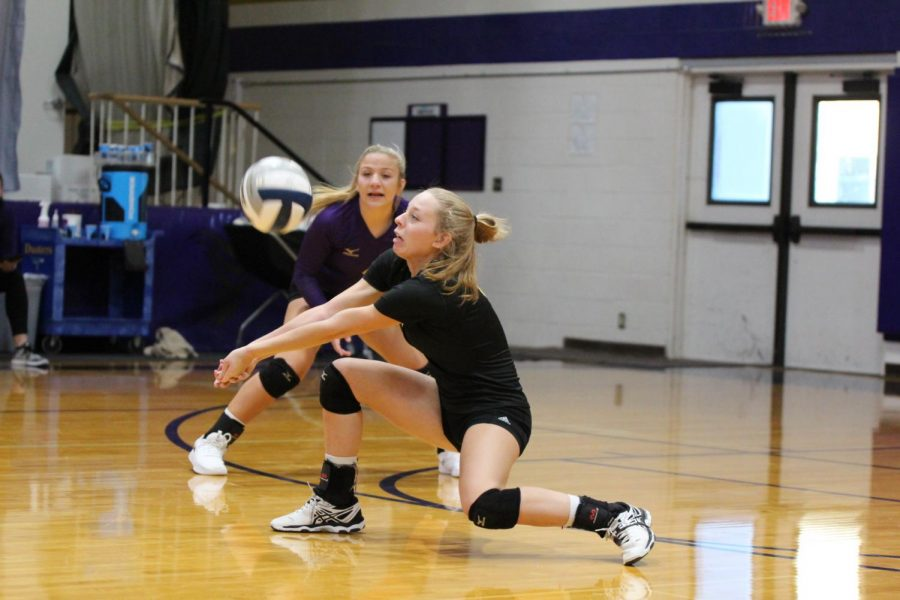 Senior Jenna Karn receives a serve during a  home game, while sophomore Taylor Wiser looks on.