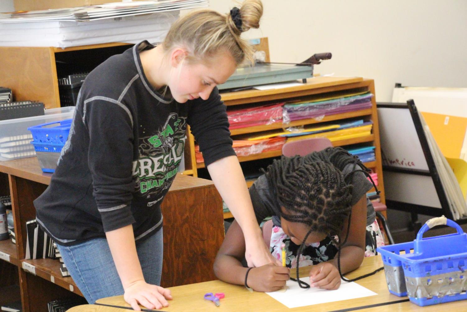 High Helper, Senior Jorjah Shimmin, helps an elementary student with her assignment.