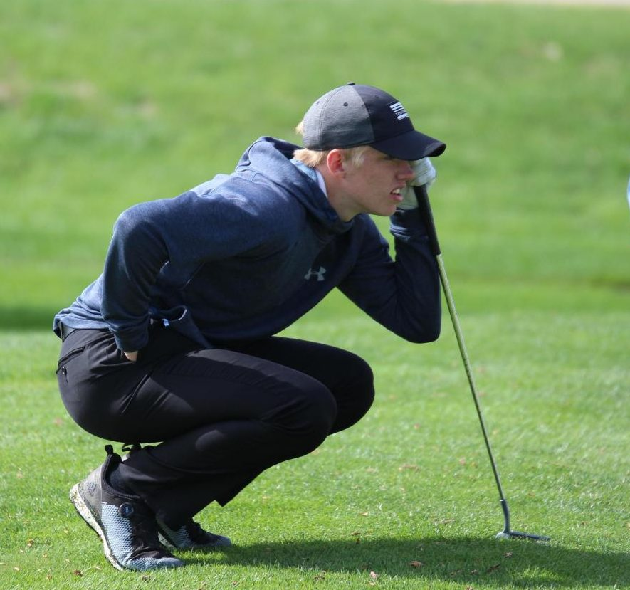 Junior Nelson Milks looks over the line of his putt on the number one green at the Holdrege Invite.